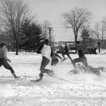 Students let off steam and kick up snow in a friendly game of snowshoe-football, 1939.