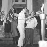 At the Statehouse in Augusta, announcer Bill Huckabee '58 looks on as David Harper '59 lights the torch signifying the start of the 1958 Winter Carnival.
