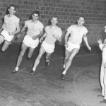 Track coach Walt Slovenski times his 1955 mile relay team, consisting of Jim Riopel, Mick McGrath, Peter Wicks, and Doug Fay.