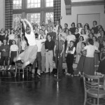 "A cheerleader instead of a choir director? (Choral Society is led in the College cheer during the recording of ""Songs of Bates,"" circa 1951.)"