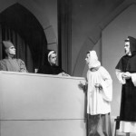 Peter Packard and Robert Damon stand, wary of inquisitors Daniel Rubinstein and David Wyllie, in the March 1955 production of St. Joan.