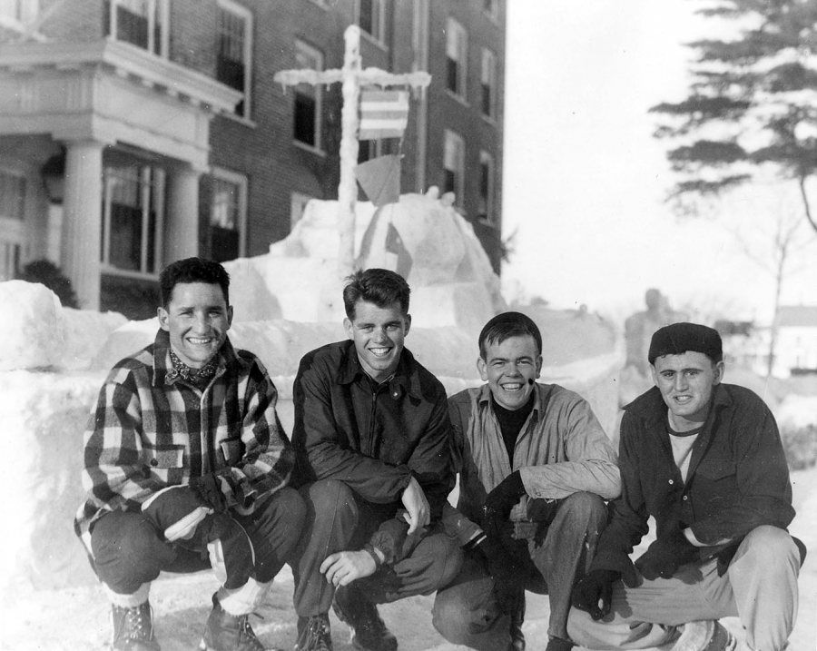 A member of the V-12 unit at Bates, Bobby Kennedy (third from left) poses in front of a Winter Carnival snow sculpture of a Navy ship. (Muskie Archives and Special Collections LIbrary)