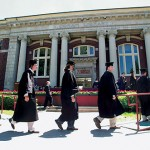 Now: (May) From left, Graham Veysey, John VanNostrand, and Eric Ursprung follow classmates to the dais during Commencement 2004, held on the Quad with Coram Library as a backdrop.  Photograph by Phyllis Graber Jensen.
