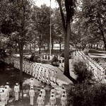 Then: (July) Attending Bates under the World War II V-12 program, Navy men in dress whites stand at attention for morning colors on the Quad. The program, which provided officer training and accelerated college instruction, had some 340 participants at Bates by 1945.  Photograph by George French, 1940s, gelatin silver print, the Edmund S. Muskie Archives and Special Collections Library.