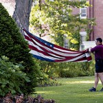 Now: (July) A Bates security officer folds the American flag at the end of a summer day.  Photograph by Phyllis Graber Jensen.