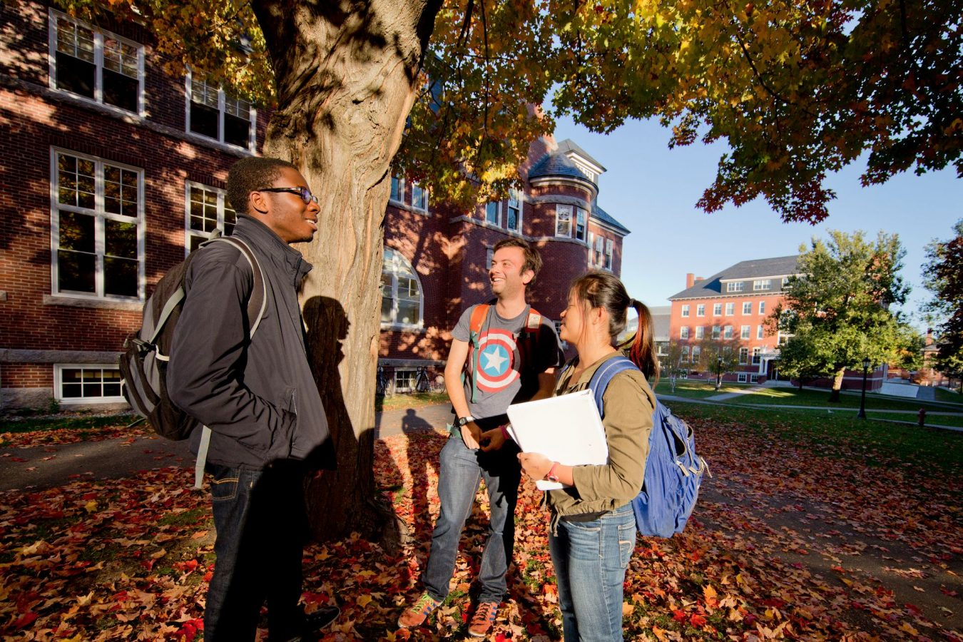 The Bates campus lights up with the brilliance of fall foliage on a late afternoon on the Historic Quad.  Annie Kandel '18 of Amherst, Mass., Matthew Winter '18 of New York City, and Durotimi Akinkugbe '18 of London, U.K. They were joined by a fourth student,