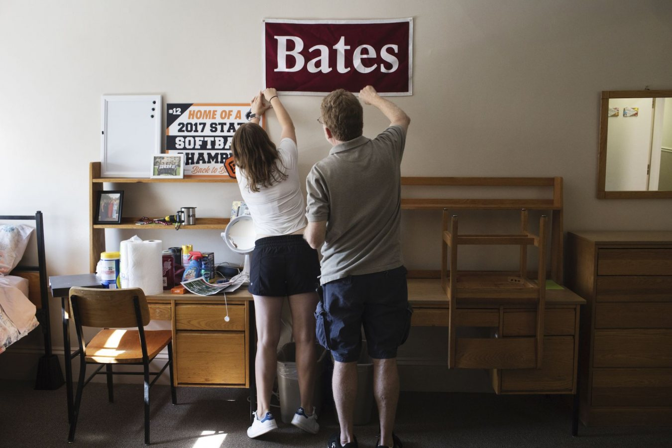 Abra Kaplan '21 of Oak Park, Ill., stretches to pin a Bates College banner on her wall with the assistance of her father Gary Kaplan while moving in to her new dorm at Rand Hall during move in day.