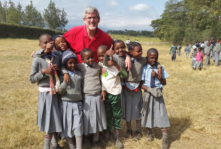 Bruce Fryer '79, awarded a Barlow Alumni Travel Grant to teach at the the Maasai Joy Children's Centre in Arusha, Tanzania, for two weeks in summer 2015, poses with some of his students during field day festivities.