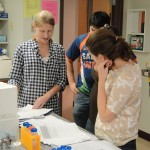TWA Missy Ducommun '11 goes over comments on a draft Introduction with a group in lab.