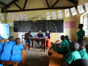 Conor Smith (center at table) moderates a student conservation education debate at Kasiisi Primary School in Uganda.
