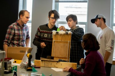 "Assistant Professor of Biology Andrew Mountcastle observes as students in his new course on ""Bioinspiration and Biomimetics"" (from left) Thad Gunther '21, Jeremy Bennett '21, Josh Turner '20, and Ruth van Kampen '19 test the performance of their 3D printed models of grooming brushes that are inspired by cat tongues. Swipe left to see a few scenes from today's lab.. The exercise was part of a course project motivated by a recent academic paper that discovered that grooming brushes inspired by cat tongues perform better than typical human hairbrushes. Cats use hollow papillae (the grooves in their tongues) to wick saliva into their fur. Student IDs: Erin Murphy '21 in denim jacket Eve Cinquino '19 in black and shite patterned pullover with Andrew Hiram Martin '19 in plaid and Elly Bengtssom '19 in red pullover With raisins: Wendy Memishian '19 in black and plaid and Bridget Tweedie '21 in paisley Gavin Chen '20 side loading scale and Brianna Karboski '21with white and pink pullover at laptop and in background Joseph Ho '20 in blue plaid. Josh Turner '20 with Sea Saba hat and Ruth van Kampen '19 in purple pullover Thad Gunther '21 in grey with snowflakes sweater and glasses with Jeremy Bennett '21 in blue plaid shirt with hood Blonde hair: Abby Hamilton '21 and Julie Hinton ;20 in cowl sweater Alex Bickart '21 tall blond hair pulling cat hair"