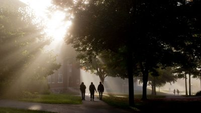 Foliage and fog go hand in hand on the Bates College campus on an early fall morning as students head to class and breakfast, crossing the Historic Quad.