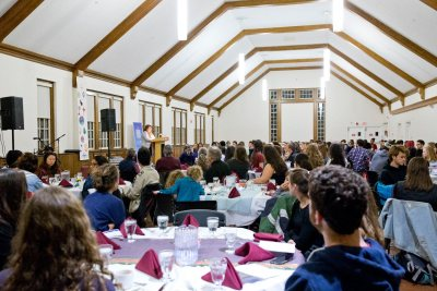 """Multifaith Banquet Wednesday, November 11, 2015 6:30-8:30 p.m. Chase Hall, High Ceiling Room A festive dinner in celebration of the religious and spiritual diversity of Bates College! Come hear your friends' stories: Gina Ciobanu, Charlotte Cramer, Tara Das, Kudzaiishe """"Irene"""" Mapfunde, Rakiya Mohamed, Mitch Newlin, Ezra Oliff-Lieberman, Caleb Perlman, Deepsing Syangtan, Emilio Valadez Blessings from our Associated Chaplains, including Rabbi Sruli Dresden from Temple Shalom, Auburn Musical Offerings by The Gospelaires, Divyamaan Sahoo & friends and Nicole Pelonzi Traditions represented include: Agnostic, Buddhist, Catholic, Christian, Hindu, Jewish, Muslim, New Age, Quaker, Seeker, Unitarian Universalist and more At table together are from left, Aria Sanders '18, Rakiya Mohamed '18 and Kenyata Venson '18. Speaking are Rakiya Mohamed '18, of the Muslim faith, and Ezra Cliff-Lieberman '18 , of the Jewish faith."""