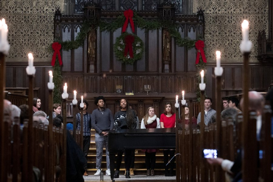"""Students gather this evening in the Peter J. Gomes Chapel for ""Candles and Carols,"" the annual candlelit service of communal singing, reflective readings from many traditions, and musical offerings by the Bates College Choir, Bates acapella groups, Mark Su'22, Amelia Keleher '21, and Music Director/Organist John Corrie. The evening was sponsored by the Bates College Multifaith Chaplaincy."