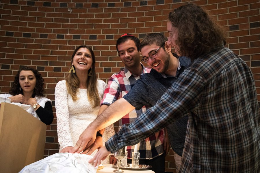 Brooke Drabkin '18 of Roslyn Heights, N.Y., Matthew Winter '18 of New York City, Evan Goldberg '19 of Belmont, Mass., and Alexis Hudes '20 of Owings Mills, Md., place their hands on a loaf of covered challah while listening to Ariel Milan-Polisar, rabbinical student at Hebrew Union College-Jewish Institute of Religion, New York City, left, while in a Shabbat Evening Service & Dinner in the Benjamin Mays Center during Back to Bates Weekend. The Back to Bates Shabbat dinner and service run by Bates Hillel. (Theophil Syslo/Bates College)