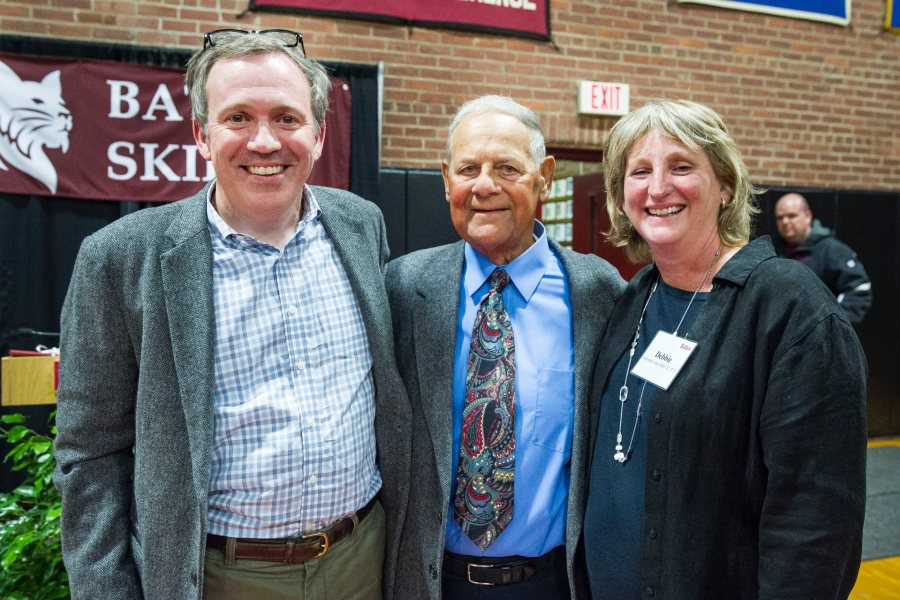 "A huge crowd of Bates skiing faithful turned out in Alumni Gymnasium during Back to Bates Weekend to recognize legendary Bates skiing, baseball, and golf coach Bob Flynn P'85, P'89 with the naming of the newly renovated Alpine and Nordic ski rooms, made possible by generous gifts in honor of Coach Flynn. Surrounded by friends and family — including his wife, Benita, daughters Becky Flynn Woods '89 (current Nordic ski coach); Elizabeth A. Flynn P'14, P'17, P'17; and Susan Flynn Dorris '85 — Flynn received a rousing chorus of ""We love you coach, Oh yes we do!"" after being lauded by Director of Athletics Kevin McHugh, President Clayton Spencer, and Bates Trustee Steve Fuller '82, P'13. Pictured here (l–r) are Bates Trustee Steve Fuller '82, P'13; Coach Flynn, and Debbie Fuller '82, P'13."