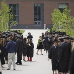 Graduates fill the Alumni Walkway, as Associate Dean of Students Holly Gurney (center) consults her program.