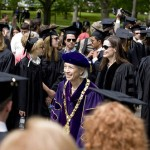 (From left) President Hansen, followed by honorary degree recipients Geena Davis, Robert Franklin and Mimi Koehl, process through two lines of graduates.