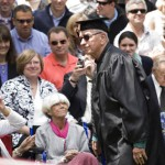 Fifty-five years after leaving Bates to join the army, Carl Harris of Salem, Mass., passes wife, Sunny (in pink scarf), to receive his Bates diploma with the Class of 2009.