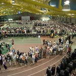Family and friends line the indoor track to watch the Commencement procession.