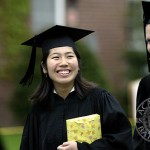 Followed by Kari Edwards (right), Yuko Eguchi carries a gift on Commencement morning.