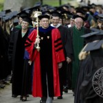 Mace bearer Sawyer Sylvester, professor of sociology and senior member of the faculty, leads the Commencement procession between graduates lining the quad.