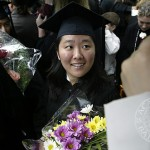 After receiving her diploma, Loretta Kim finds shelter under an umbrella.