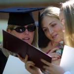A member of the Class of 2002 shares her diploma with family members.