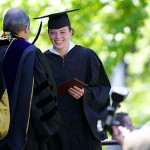 Louisa Jensen smiles for the cameras as she receives her degree.