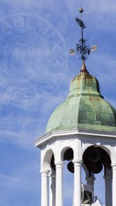 Bates seal over blue sky with weathervane