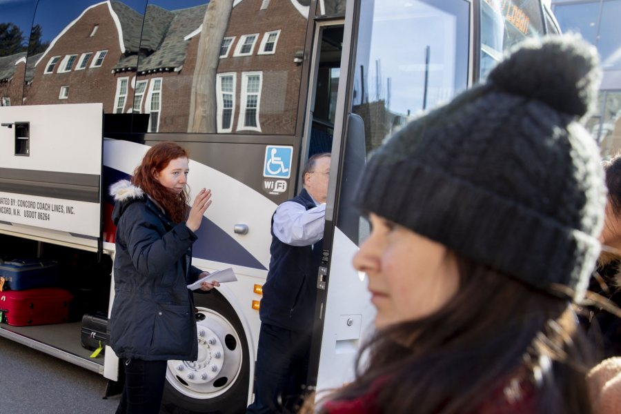 Students gather in front of Chase Hall to take two buses that will take them on the first leg of their trips home. One is a Concord Trailways bus, regularly scheduled daily for 3:30 p.m. pickup. The other is a bus chartered by the College.