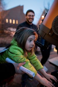 All kids agree; the moon looks WAY better up close! . Isla Shea, 6, of East Auburn School, uses a Carnegie telescope with 2,000x eye strength to view the moon as Evan Goldberg '19 looks on during last night's Bates Astronomy Extravaganza co-hosted by the Harward Center for Community Partnerships and the Bates College Physics and Astronomy Department. . Students in Astronomy 106, taught by Assistant Professor of Phyiscs Aleks Diamond-Stanic, ran hands on activities and planetarium shows to introduce children to black holes, galaxies, moons, planets, and more. Bates provided a fun night of getting kids excited about science.