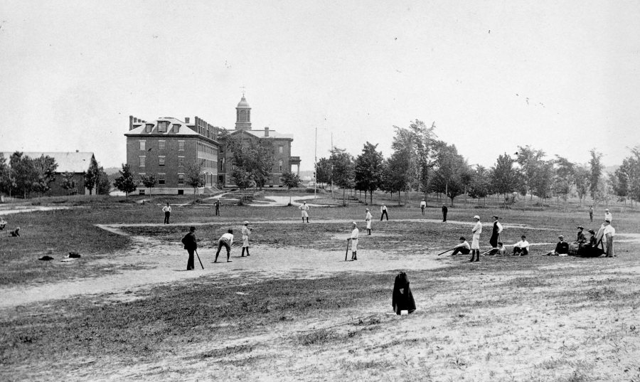 This view of baseball action in 1882 on the old Rand Field is from the base of Mount David. Parker and Hathorn halls are at center background. The original Bates gymnasium is at far left. (Muskie Archives and Special Collections LIbrary)