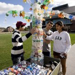 """Reuse, Rebuild, Reward!"" a contest asking students to use recyled materials and creativity, yields some wild results. From left, Mike Pasek '12 joins Walter Garcia '11 and Shirley Serrao '11 , JAs from 289 College Street, in displaying this colorful sculpture, a collaborative effort of the house's first-year students."