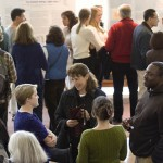 A poster session on student research and service-learning attracts many visitors, students, faculty and staff to the Perry Atrium on Friday afternoon.