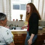Helping with lunch cleanup, Kate Marshall '04 chats with Maria, the maid for her home-stay family