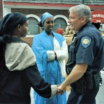 During the downtown Somali support rally in October 2002, a Somali woman and Lewiston police officer greet each other as Zam Zam Mohamed (in blue) looks on
