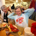 Jo Trogler Reynolds '58 gets ready to dive into her lobster dinner as Nancy Tyler Harris '59, whose husband is Kenneth '58, looks on.