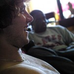 Bates College, 9:47 a.m.  AMONG FRIENDS Anthony Arger '06 of Reno, Nev., shoots the breeze with friends, including Eric Obeng '07 (seated behind), in Suite 141 in Moody House.