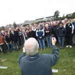 Opening the Bates-Bowdoin football game at Garcelon field on Nov. 3, Jim Curtis '63 conducts more than 80 alumni and current Deansmen in singing the National Anthem. The event was part of the a cappella group's 50th anniversary celebration. Photograph by Phyllis Graber Jensen.