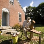 Outside the couple's brick farmhouse, neighbor Ian Ormon, seated at a shaving horse built by Morse, uses a drawknife to shape oak pegs the traditional way.