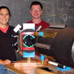 "Batavia, Ill., 8:47 a.m.   MEGA PIXELS At the Fermi National Accelerator Laboratory, husband-and-wife physicists Brenna Flaugher '83 and Tom Diehl '82 stand with a scale model of the Dark Energy Camera, their current project. At 500 million pixels, it will be the world's largest digital camera and will be mounted on a telescope in the Andes to examine ""dark energy"" and ""dark matter."""
