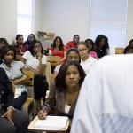 "In Lisa D'Oyen's psychology class at Spelman, ""Risky Behavior: HIV and AIDs,"" she and her classmates listen as a HIV/AIDS activist tells his story and discusses the vulnerability of young African Americans to the disease. Seated at left is Assistant Professor of Psychology Angela Farris Watkins."