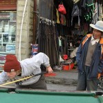 A Tibetan man watches Sumner Crosby '08 shoot pool during a stop along the road for food.