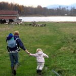 Salisbury, Vt., 9:47 a.m.  GETTING THEIR GOATS At Blue Ledge Farm, Hannah Sessions '99, daughter Livia, and baby son Hayden move goats in the pasture. A sustainable goat dairy and cheesemaking operation, the farm is owned by Sessions and husband Greg Bernhardt '99, who, after taking this photo, adjourned to the cheesehouse to pour curds for fresh chevre.