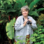 "Paraíso, Costa Rica, 8:47 a.m.   COFFEE BREAK Linda Moyher '67 does some birding at Finca Cristina, her organic coffee farm, which also supports a great variety of birds — ""273 species, of which 87 are migratory, including a crested caracara that just flew in!"" she says."