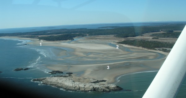 This aerial photograph of Popham Beach on March 10, 2010, shows key elements of erosion: (1) the new channel cut by the Morse River last winter, which should save the beach; (2) the old channel that for years had eroded the west side of Popham; (3) the tombolo that makes it possible to walk to rocky Fox Island at low tide. Photograph by John Picher.