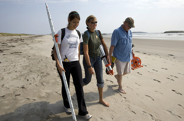 From left, thesis students Dana Oster '09 and Emily Chandler '09 walk with geologist Mike Retelle at Popham Beach and the adjacent shoreline near Bates-Morse Mountain Conservation Area. Together they monitored sand transport and erosion, using tools like automatic level, used to measure the elevation from the water's edge to the higher ground of the beach, and a stadia rod. Photograph by Phylis Graber Jensen.