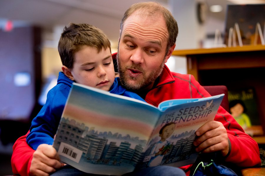 "Matt Schlobohm '00 reads a book with his son Avery, 6, in Ladd Library during the 2018 Martin Luther King Jr. Day workshop ""Friends Across Difference."" (Phyllis Graber Jensen/Bates College)"
