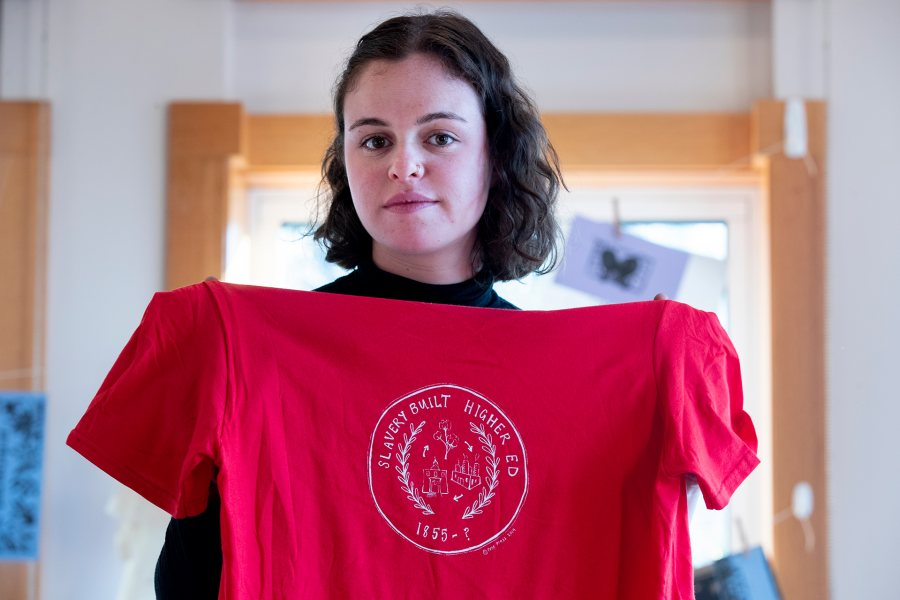 "MLK Day presenter Emma Soler '20, whose yearlong history thesis examines how the role of revenue from slave-picked cotton in the origins of Bates College, poses with a shirt she made during the November 2019 ""Free Press Bates"" printmaking event. (Phyllis Graber Jensen/Bates College)"